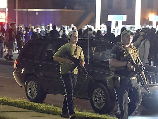 Kyle Rittenhouse, at left in backwards cap, walks along Sheridan Road in Kenosha, Wis., at around 11 p.m. Tuesday, Aug. 25, 2020, with another armed civilian Tuesday night. Less than an hour later Rittenhouse, a 17-year-old from Illinois, is accused of shooting three other people, killing two of them, with at least two of the shootings captured on video by onlookers showing Rittenhouse as the shooter. The incident took place after curfew in Kenosha less than 72 hours after demonstrations and riots broke out in the lakeside city following the police shooting of Jacob Blake.