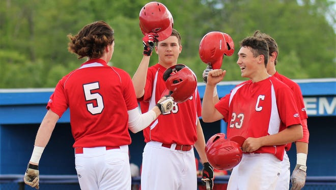 Canton players raise their batting helmets to toast teammate Justin Dolney (5) after he blasted a three-run homer in the third inning of Tuesday's pre-district game.