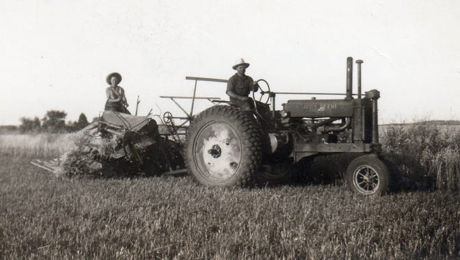 Mary Ann Primus on the binder, with her brother Paul on the tractor, circa 1940.