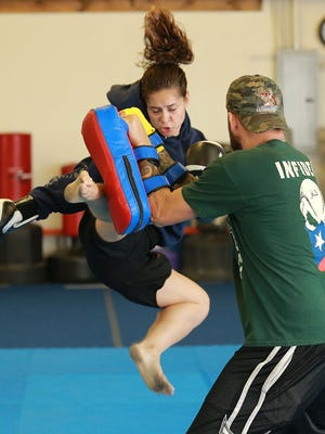 """Cynthia """"Sin"""" Arceo delivers a flying kick to the pads of Shane Schuman during a workout at United Shotokan Karate. Arceo is preparing for a bout Oct. 31 on the MavTv's King of the Cage Thunder card at the Socorro Entertainment Center."""