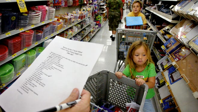 In this file photo, Danielle Olson's eyes wander the store shelves as her brother Eric (behind Danielle) asks their mother, Dorine, what's next on the list of school supplies at the North Naples Walmart on U.S. 41.