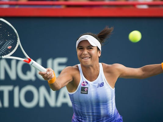 Heather Watson, of Britain, reaches for the return to Samantha Stosur, of Australia, during their first round match at the Rogers Cup tennis tournament in Montreal, Monday, July 25, 2016. (Graham Hughes/The Canadian Press via AP)