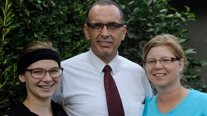 """Rev. Mark Wilson, 51, is surrounded by his youngest child, Hannah, 17, left, and his wife, Valerie, 50, at their Visalia home. He's getting back into the swing of things as pastor of Sierra Baptist Church in Visalia following a cycling accident that left him with a brain injury and loss of sight in his right eye. """"I'm doing better all the time,"""" he said."""