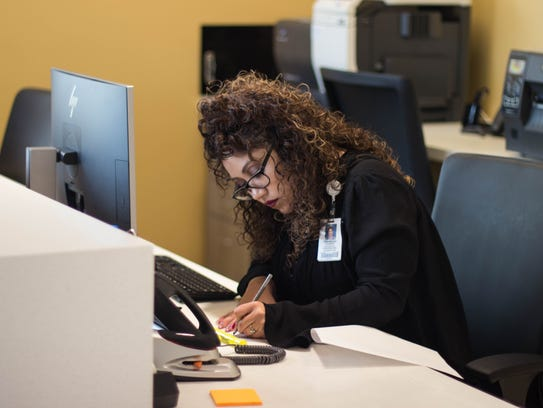 Front desk operator Kassandra Espinoza handling paperwork