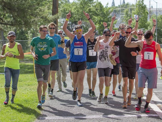 Dave Zaski, center in blue, leads his team the Runny Bums across the finish line during the 12th Annual Reno-Tahoe Odyssey Relay Run last year