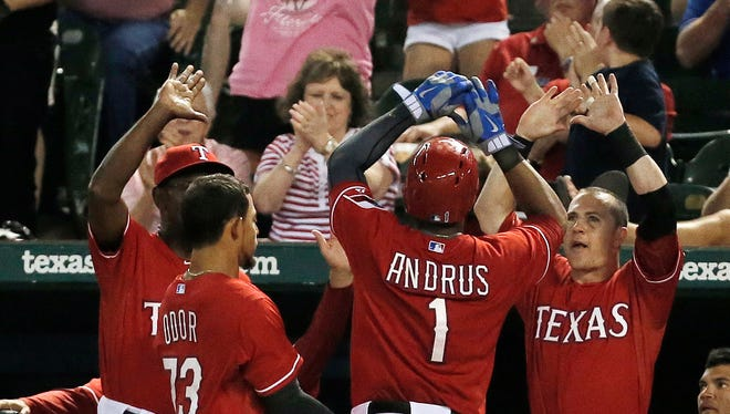 Texas Rangers Elvis Andrus (1) is congratulated by teammates after scoring a run on teammate Adrian Beltre's sacrifice fly during the eighth inning of a baseball game against the Cleveland Indians, Friday, June 6, 2014, in Arlington, Texas. Texas won 6-4.