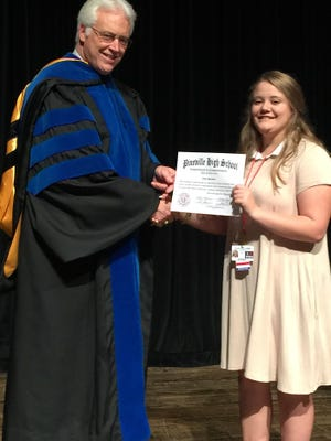 "Pineville High School Principal Karl Carpenter gives freshmen ""commitment to commencement"" certificates during an event planned to help students stay on track for graduation."