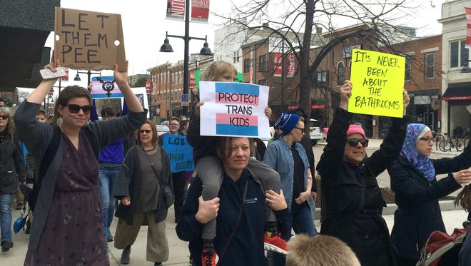 Dozens of supporters march along Washington Avenue in downtown Iowa City on Sunday afternoon to protest President Donald Trump's recent reversal of the Obama Administration's guidance on transgender bathroom protections in public schools.
