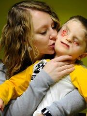 Lacey Buchanan kisses her son Christian.
