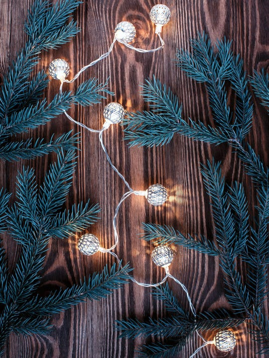 Christmas composition with vintage garland and blue fir branches on wooden background.String lights.