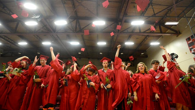 Members of the Paris Gibson Education Center Class of 2014 toss their caps at the conclusion of the spring graduation ceremony Tuesday evening.
