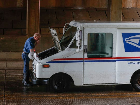 A U.S. Postal Service truck sits stranded on Grand
