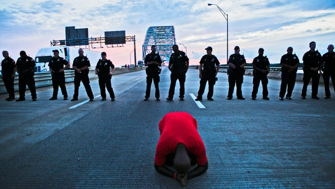 Pastor Rickey Scott, 44, with New Change Church, kneels as he prays in front of Memphis police officers during a Black Lives Matter protest on I-40 in Memphis in 2016.