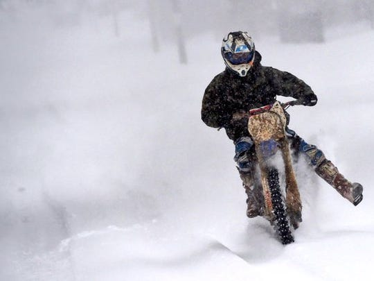A man rides a motorbike during a snow storm on Saturday,