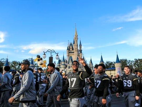 Central Florida football players walk in front of Cinderella's Castle during the a parade at Walt Disney World in the Magic Kingdom on Sunday, Jan. 7, 2018, in Orlando, Fla. (Jacob Langston/Orlando Sentinel via AP)