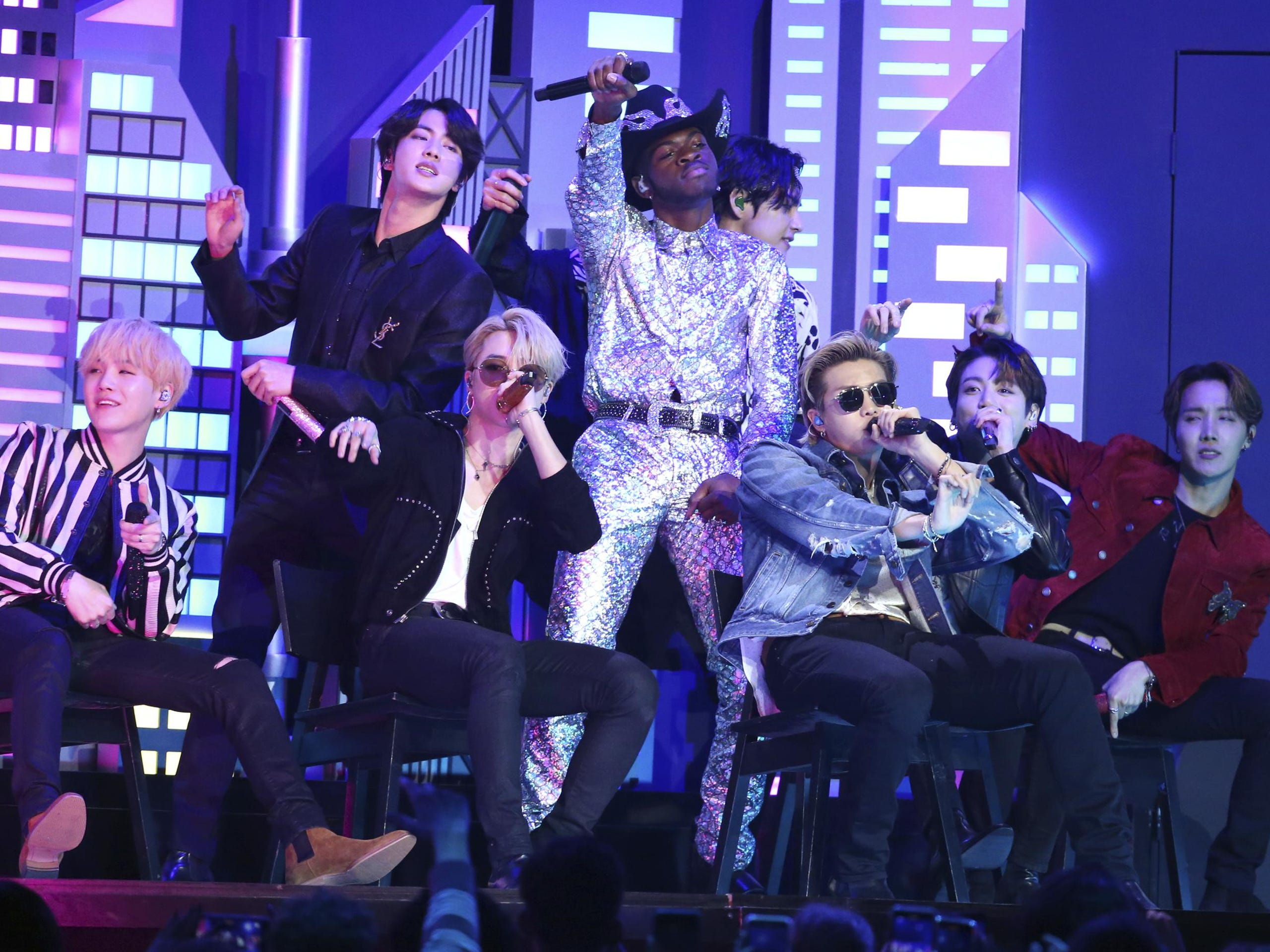"""Lil Nas X, background center, performs """"Old Town Road"""" with members of the South Korean pop group BTS at the Grammy Awards on Jan. 26, 2020. """"Dynamite,"""" the group's first all-English song, debuted at No. 1 on the U.S. music charts this week, making BTS the first Korean pop act to top the chart."""