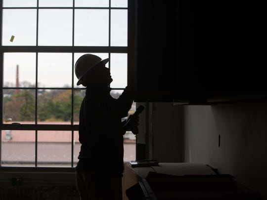 Trey Wiseman installs cabinets at the Lofts at Clifford Brown Walk on Nov. 12. A former abandoned warehouse is being turned into 80 affordable housing lofts along the banks of the Brandywine in Wilmington.