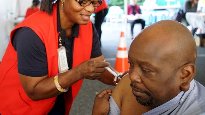 Justina Okereh, a registered nurse, gives a flu shot to Robert McLaurin at a Division of Public Health free flu shot clinic in 2016.