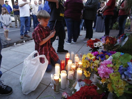 Layten Gassett, the son of one of the victims of a shooting rampage, lights candles in honor of his father during a candlelight vigil Thursday, April 20, 2017 in Fresno, Calif.
