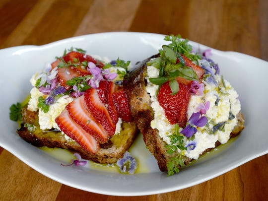 Tartines made by OWL Bakery are fresh homemade ricotta cheese on double raisin and flax bread topped with strawberries, olive oil and candied herbs and flowers.