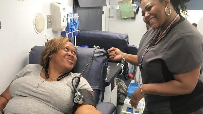 Natasha Langford, of North Augusta, gets prepped to give blood by Tinisha Washington at Shepeard Community Blood Center's mobile donation unit outside Carey Hill Baptist Church in North Augusta. Shepeard said It is currently at a critical need level which means the quantity of ready blood and blood products is below a one-day supply. .