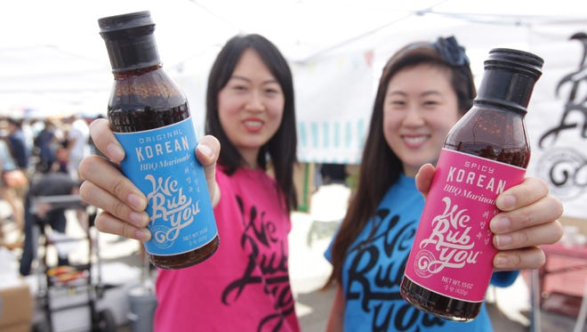 """Ann and Janet Chung, co-owners of """"We Rub You,"""" a Korean style cooking sauce company, at the Brooklyn food fair called """"Smorgasburg""""."""