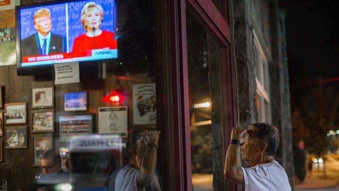 A man watches the presidential debate between Hillary Clinton and Donald Trump from outside Manuel's Tavern on Sept. 26, 2016, in Atlanta.
