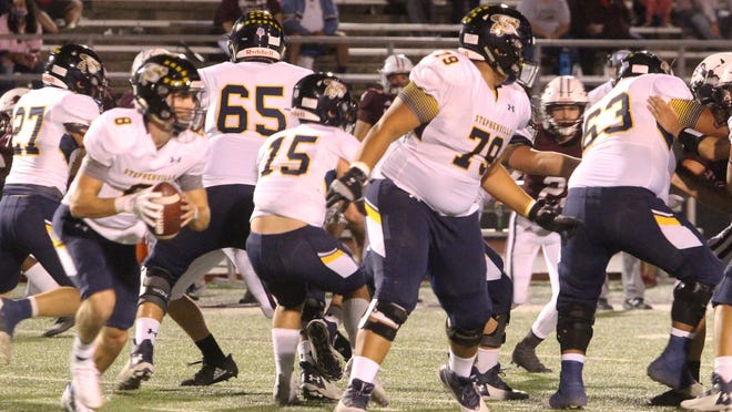 Stephenville players set up a wall of protection for quarterback Gavin Rountree (8) as he looks for a receiver on a rollout during Friday's district football opener in Brownwood.