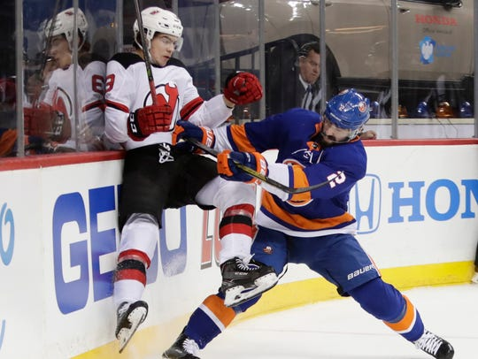 New York Islanders' Nick Leddy (2) checks New Jersey