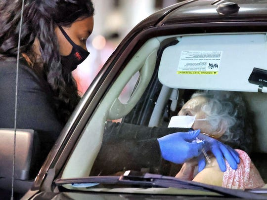 A Florida resident gets vaccinated at the drive-thru site at the Orange County Convention Center in Orlando on Monday.