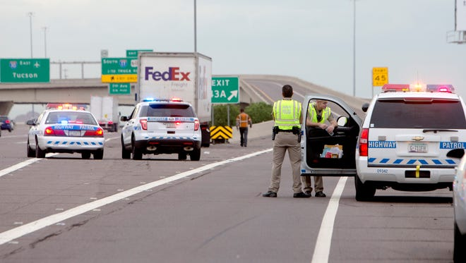 Arizona Highway Patrol troopers clear the scene of a multiple vehicle accident on Interstate 10 eastbound near Interstate 17 that closed three lanes Tuesday morning.