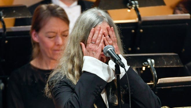 Patti Smith covers her face when performing 'A Hard Rain's A-Gonna Fall' by absent 2016 Nobel literature laureate Bob Dylan during the 2016 Nobel prize award ceremony at the Stockholm Concert Hall on Dec. 10.