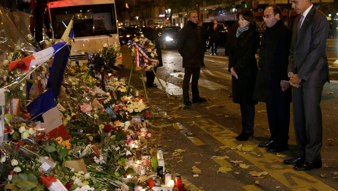 U.S. President Obama, French President Francois Hollande and Paris Mayor Anne Hidalgo pay tribute to the victims of the Nov. 13 attacks in front of the Bataclan concert venue on the eve of  the opening of the COP21 Conference in Paris Monday.