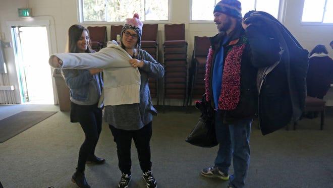 Volunteer Isabel Garcia, 20, helps Krystal Herren, 29, into a sweater while Herren's husband, Hawkeye Morgan, 37, looks on in this Dec. 25, 2016 photo. Volunteers helped 120 homeless people during the sixth annual Room at the Inn event in Turner, Ore.