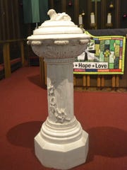 The baptismal font stands at the front of the altar