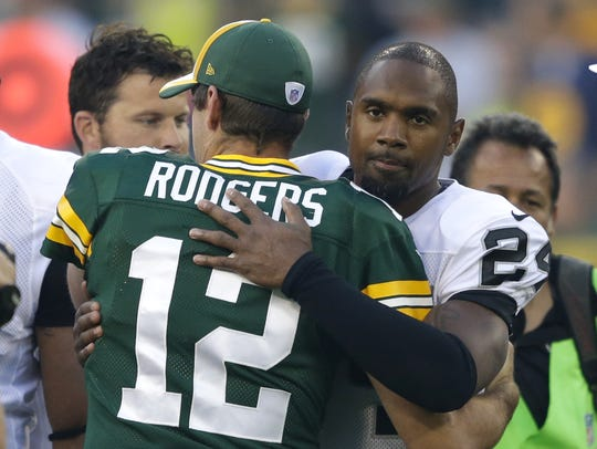 Oakland Raiders safety Charles Woodson embraces Green