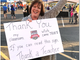 A teacher holds a sign thanking those who helped grant
