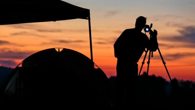 Jim Cleveland, of Shelbyville, Ky., sets up a camera at his campsite at sunrise as he prepares for the solar eclipse Aug. 21, 2017, on the Orchard Dale historical farm near Hopkinsville, Ky.