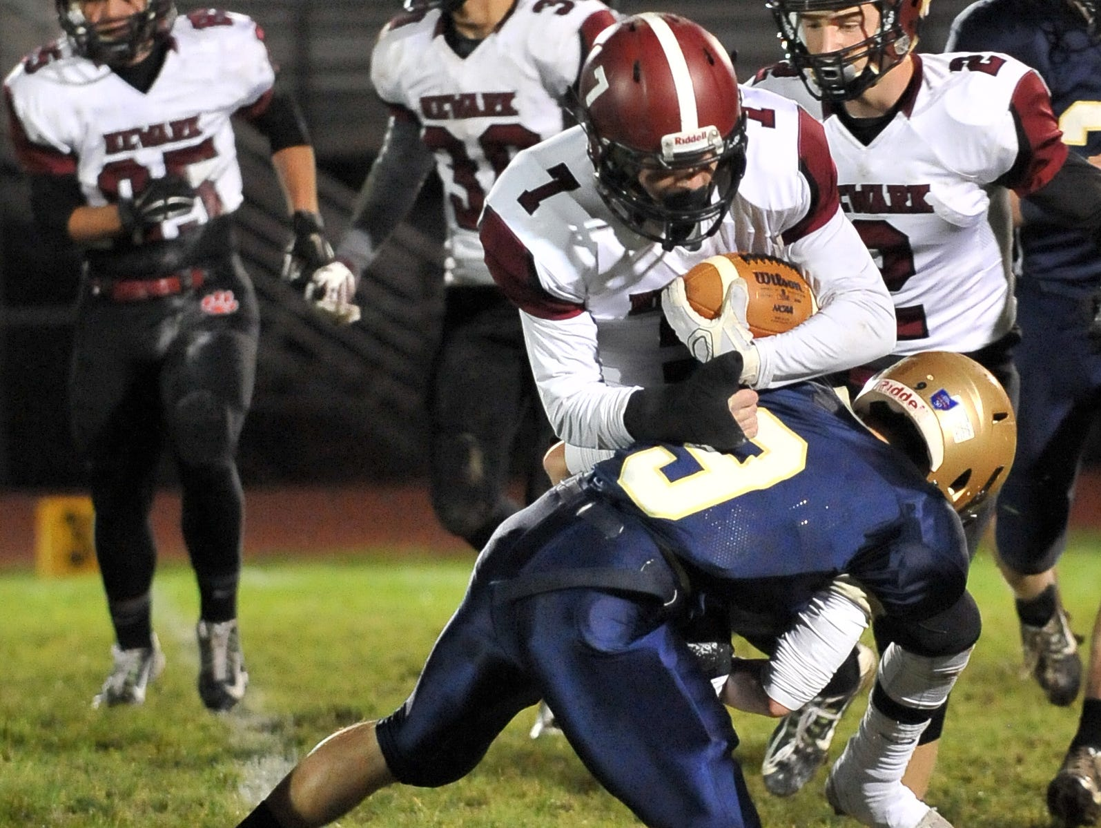 Newark's Doren Barrett is tackled by Lancaster's Ashton Walker during Friday night's game at Fulton Field in Lancaster. The Wildcats lost the game 38-7.