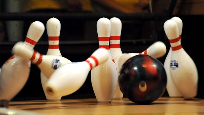 A bowling ball strikes the pins.