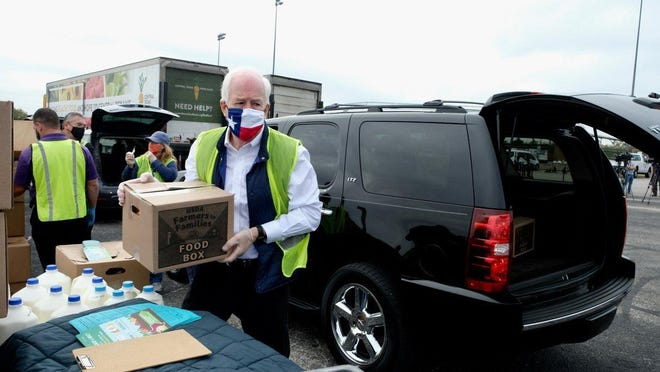 U.S. Sen. John Cornyn, R-Texas, helps with Central Texas Food Bank distribution at Burger Center on Monday.