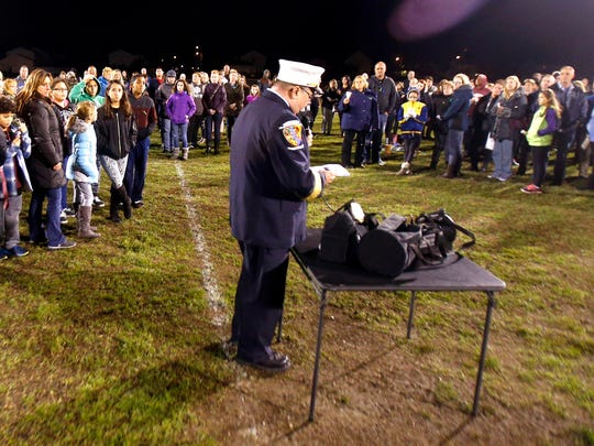 People gather on a field at the Toms River Intermediate