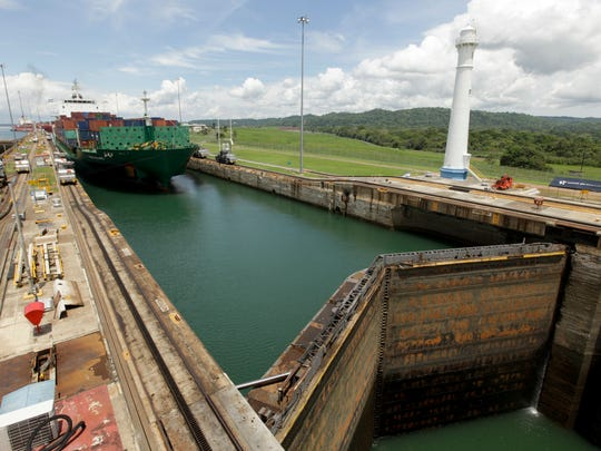 In this May 30, 2016 photo, a cargo ship leaves the Gatun locks while traveling through the Panama Canal in Gatun, Panama. Few public works projects have captured the world's popular imagination like the Panama Canal, which was built between 1881 and 1914 and revolutionized the shipping industry by connecting the Atlantic and Pacific, short-cutting sea voyages around the tip of South America. Since passing from U.S. to Panamanian control in 1999, the canal and related economic activity have come to contribute nearly 40 percent of the Central American nation's GDP.