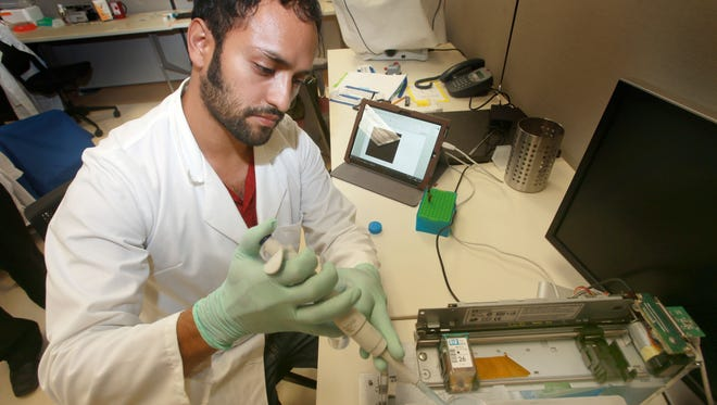 Research assistant  Julio Rincon places a mixture of magnetic microscale beads which latch onto the CD4 cells in the blood into a device which can monitor the health of HIV patients in as little as 20 minutes. The device counts the total number of CD4 cells in a person's body.