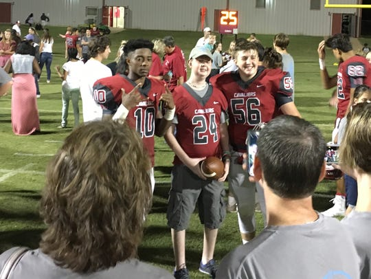 Wesley McCall (24) stands with Crockett County football players Kerrington Parker (10) and Braven Harton (56) in this 2017 photo.
