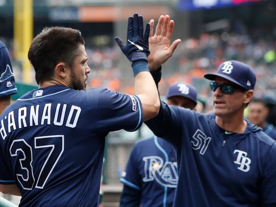 Tampa Bay Rays' Travis d'Arnaud is greeted by hitting coach Chad Mottola after hitting a two-run home run during the fourth inning of a baseball game against the Detroit Tigers, Thursday, June 6, 2019, in Detroit. (AP Photo/Carlos Osorio)