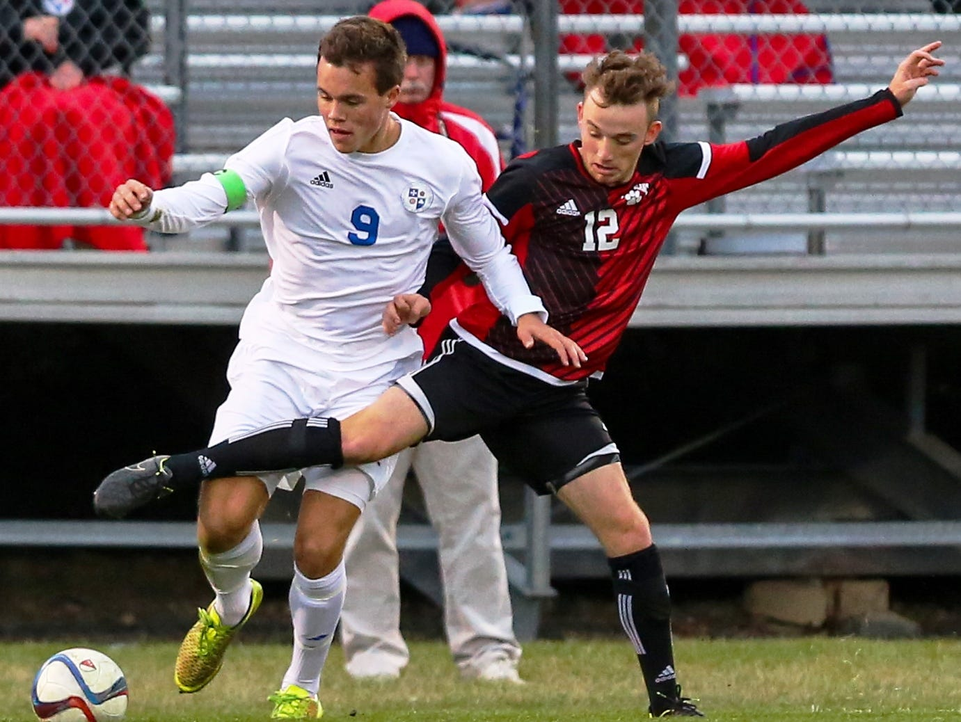Catholic Central's Justin Murray (left) tries to keep possession against Grand Blanc's Dayton Rush.