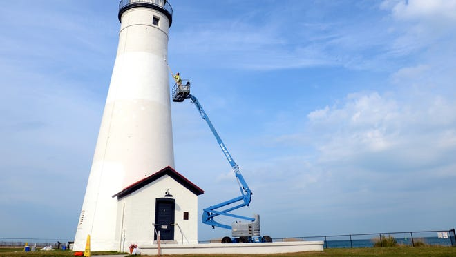 Painter DJ Lopiccolo, of Port Huron, adds a layer of paint to the lighthouse Monday, Oct. 12 at the Fort Gratiot Light Station.