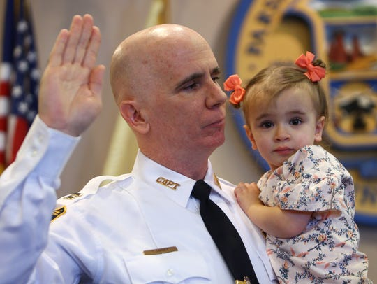 Parsippany Captain Tom Carney holds daughter Avery, 3, at his swearing in at the Parsippany Municipal Building on March 15, 2018.
