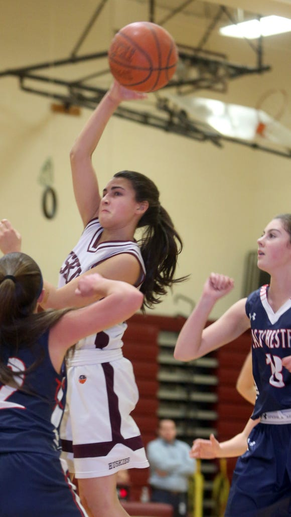 Harrison's Avery LaBarbera gets rid of the ball while being defended by Eastchester's Julie Murtagh during a varsity basketball game at Harrison High School Feb. 3, 2017. LaBarbera scored her 1000th career point in a game won by Eastchester 65-62.